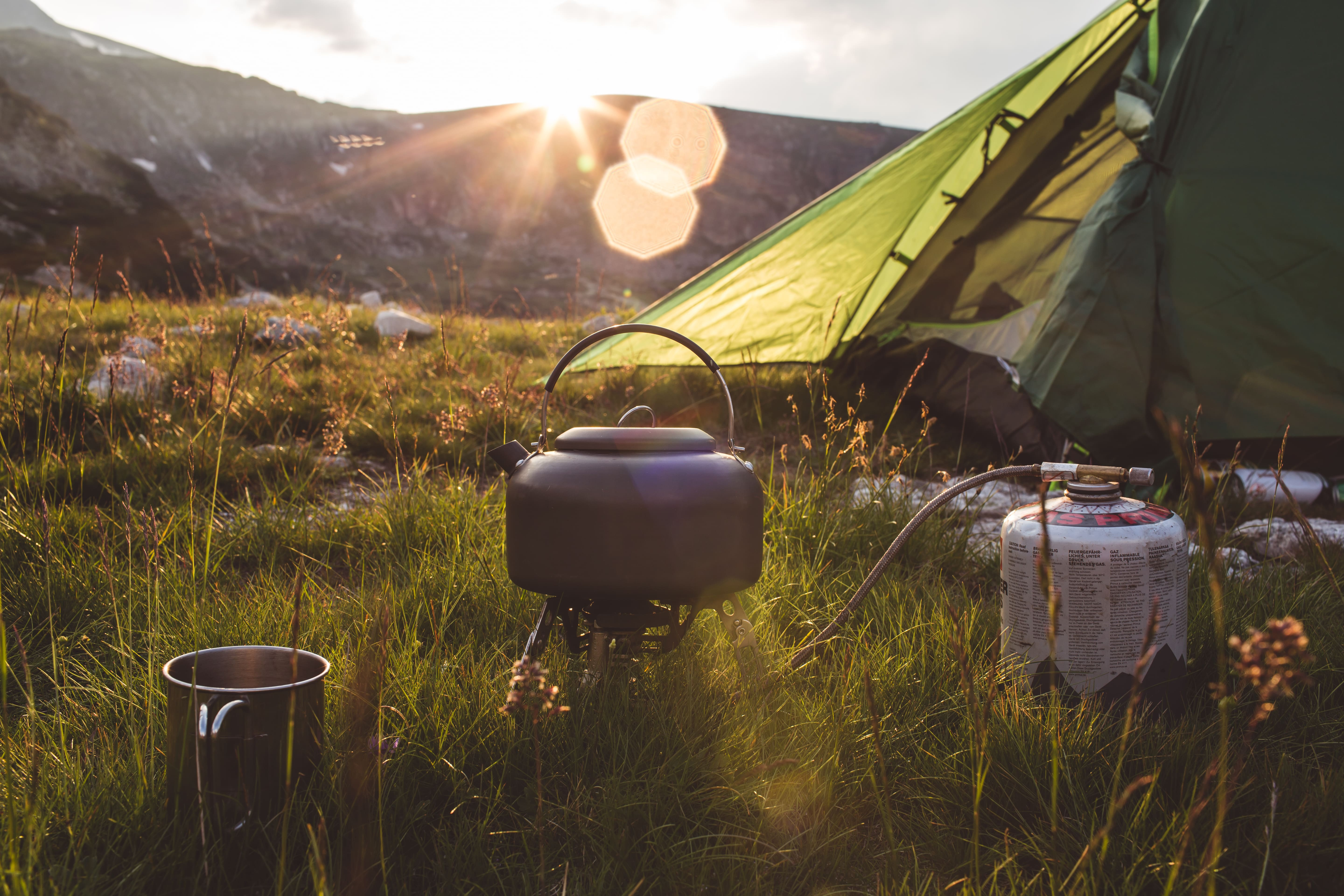 Camping teapot and cap on the grass at sunrise time